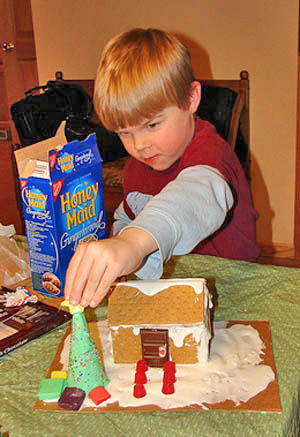 boy making graham cracker houses